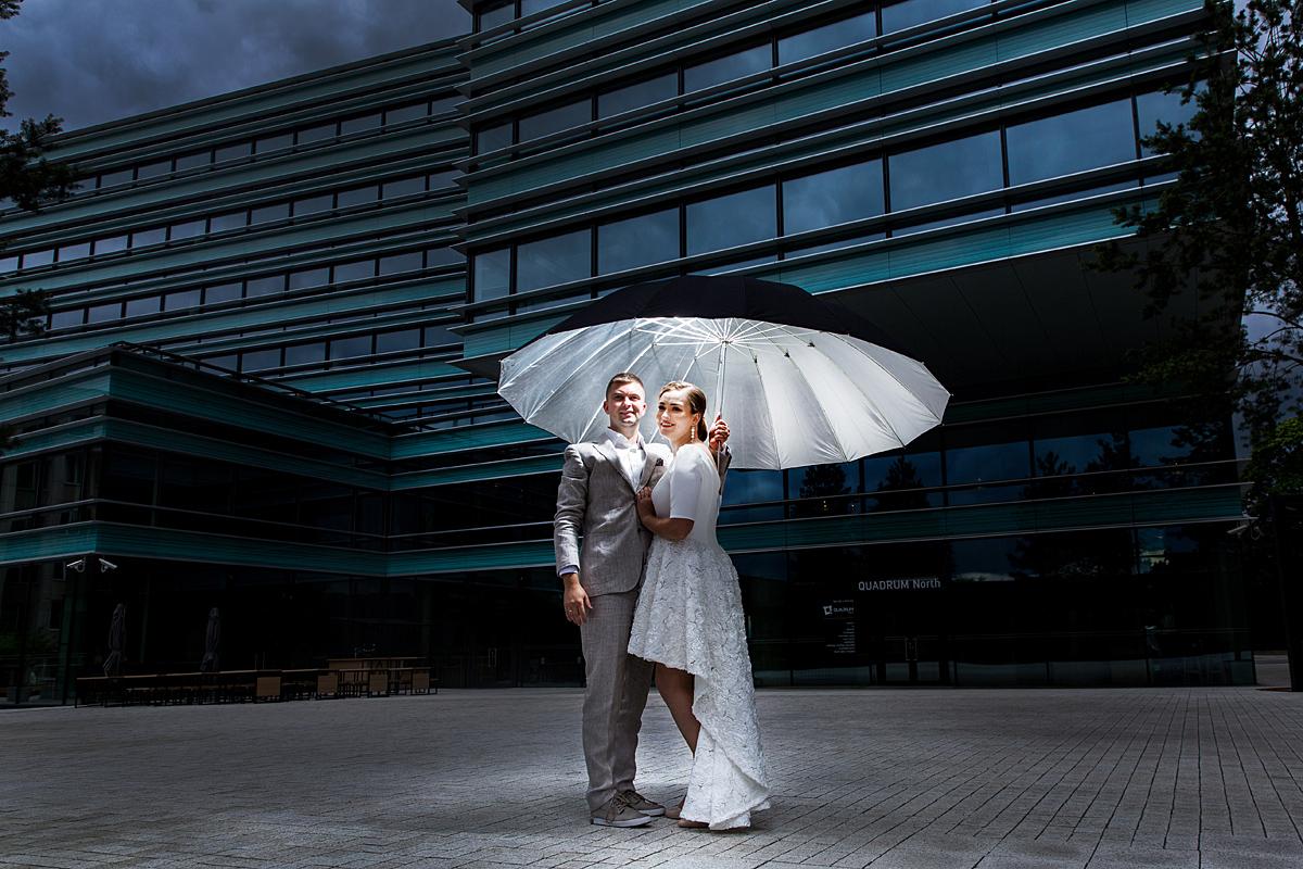 jaunieji po skėčiu, vestuvinė nuotrauka, šypsenos, šviečiantis skėtis, verslo centras, tamsiau, blico šviesa