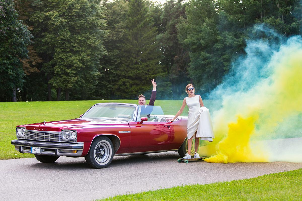 vintažinė mašina, riedlentė, crazy jaunieji, dūmai, netradicinė vestuvių nuotrauka