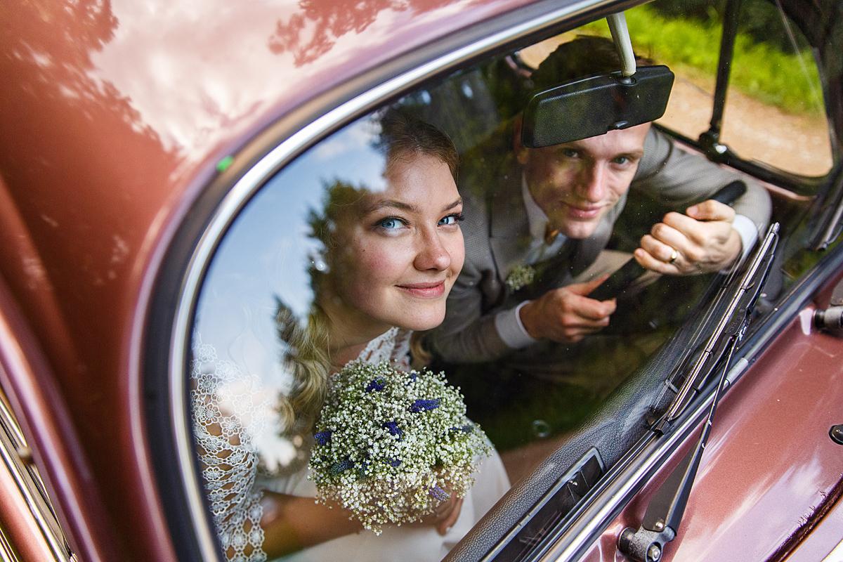 jaunieji mašinoje, vestuvių transportas, žvelgia pro langą, nuotakos puokštė, vestuvių fotografas Kaune