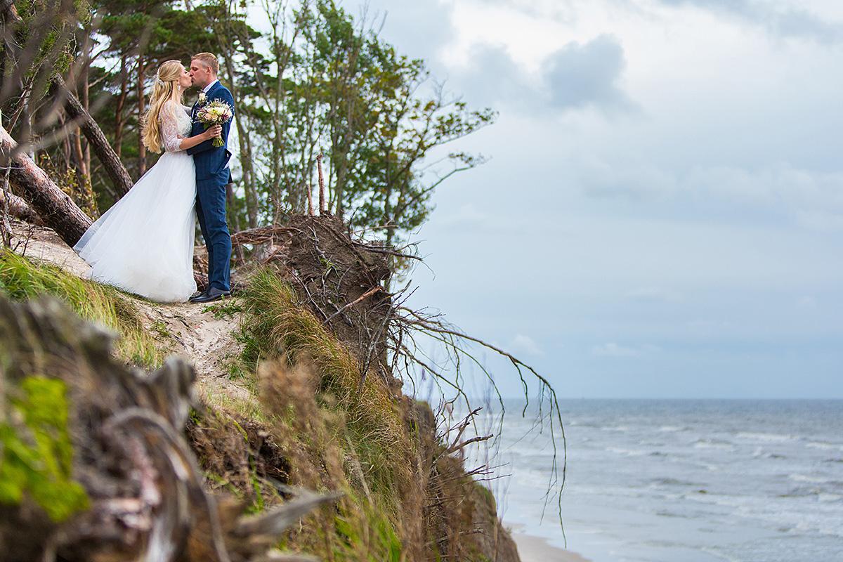 vestuvių kadras pajūryje, jūra, skardis, olando kepurė, jaunųjų bučinys, vestuvių fotografas Klaipėdoje