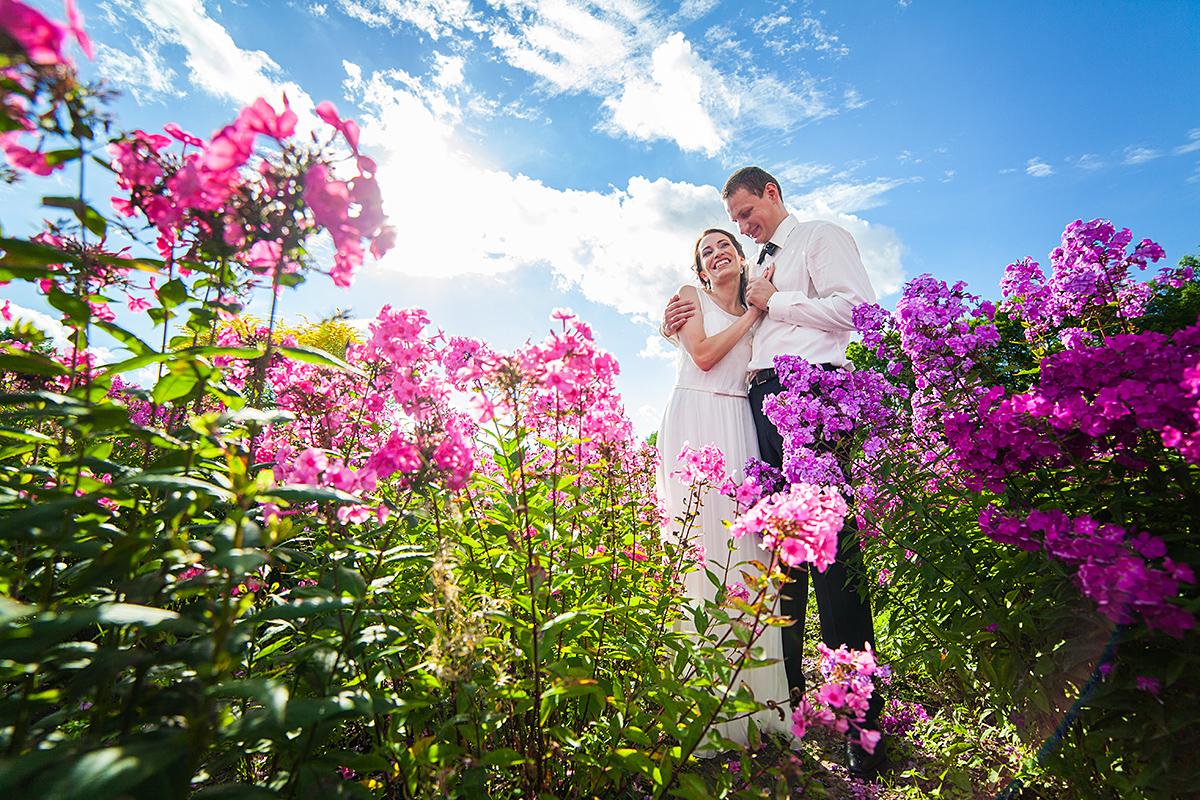 jaunieji lauke, gėlės, vestuvių kadras, mėlynas dangus, fotografas vestuvems