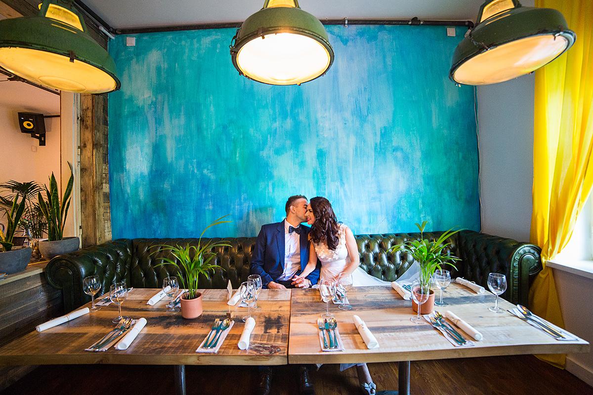 jaunieji sėdi, restoranas, vestuvių pokylis, lempos, spalvota siena, panama food garden