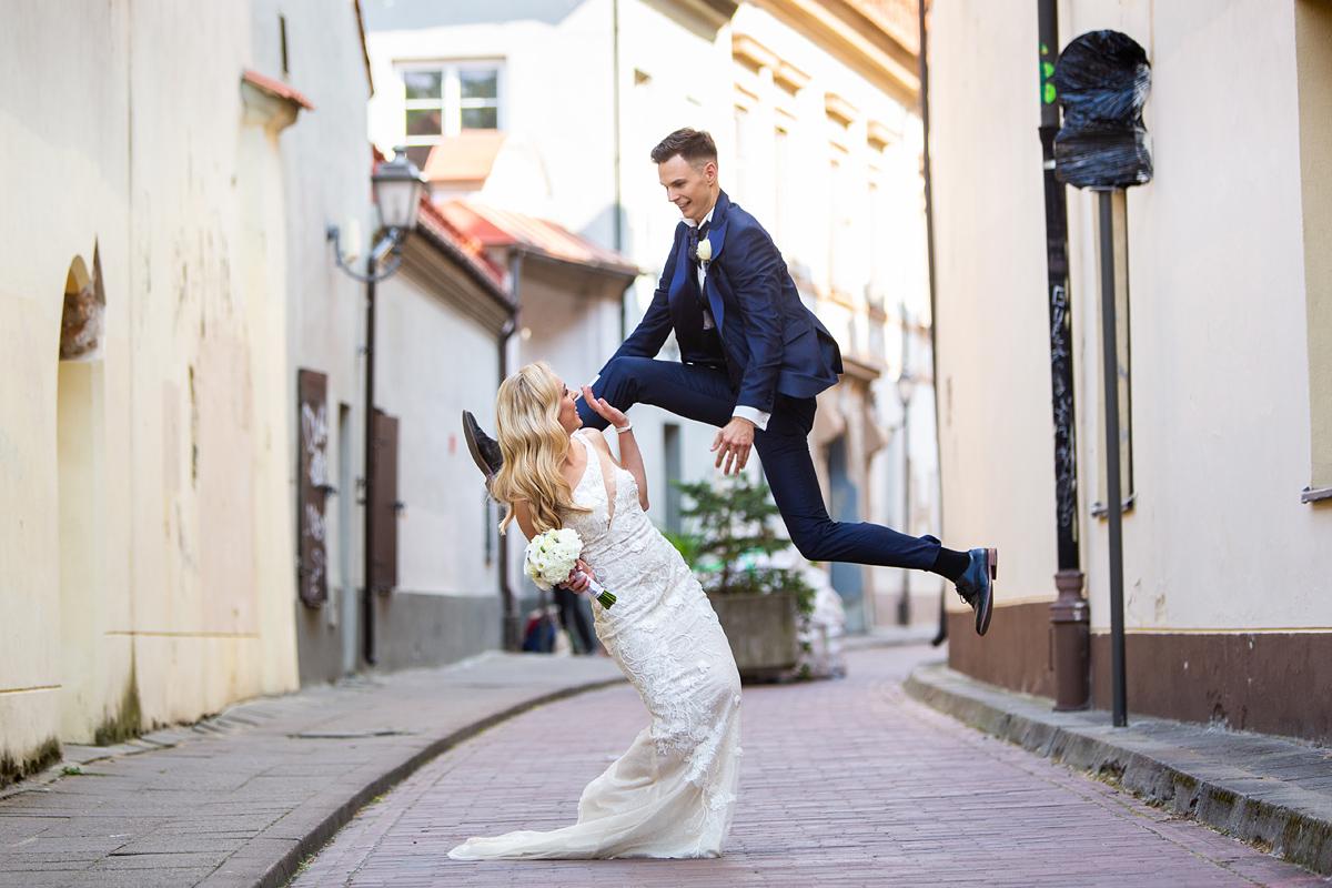 jaunikio šuolis, įdomus vestuvių kadras, vilniaus senamiestis, vilnius, vestuvinė nuotrauka