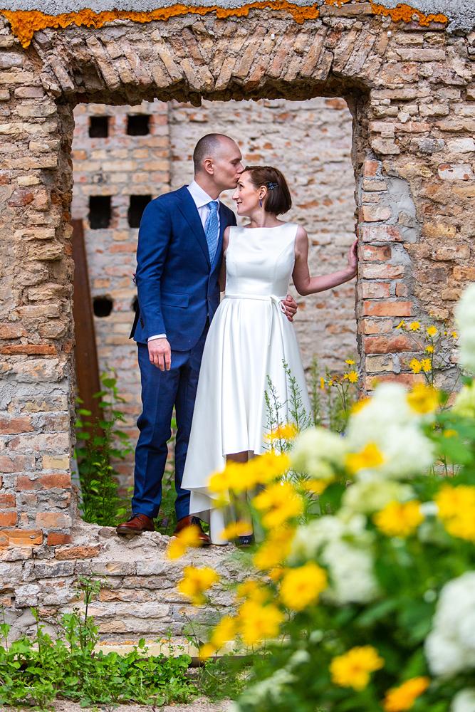 jaunųjų bučinys, vestuvių fotosesija, senovinė lokacija fotosesijai, žydinčios gėlės
