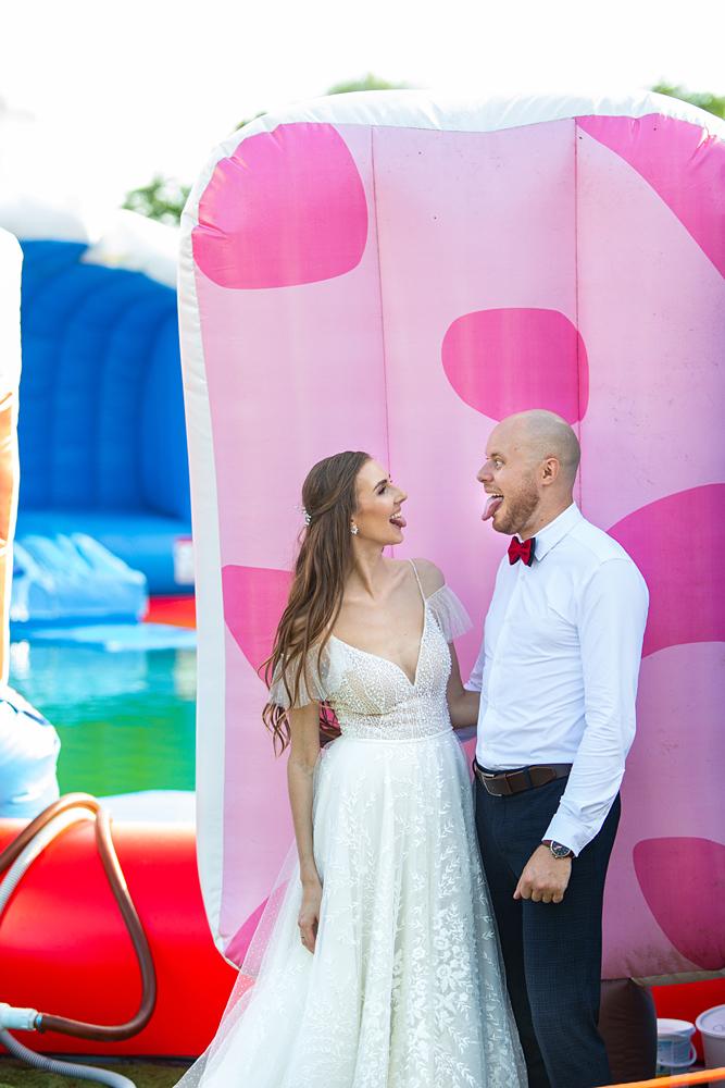 crazy vestuvių fotosesija, spalvotas fonas, jaunųjų liežuviai, vestuvinė nuotrauka